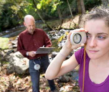 Outdoors, near a stream. Man recording research and woman using instrumentation.